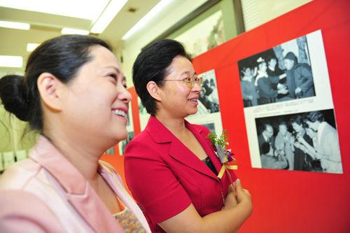 惠州市委常委、宣传部长黄雁行(右)参观中新社成立六十周年图片展