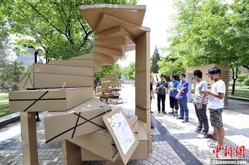"""5月14日,在山西太原理工大学,学生们利用包装箱纸、塑料布等废旧用品为原材料进行设计,建造出许多造型新颖的""""环保房屋"""",吸引了不少大学生驻足观看。中新社发 韦亮 摄"""