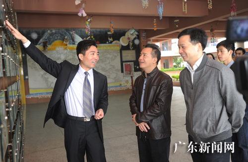 共青团省委副书记梁均达(中)等参观育才四小团队活动展示栏