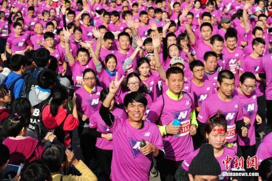 12月14日,2014年New Balance慢跑英雄联盟在深圳湾体育中心开跑,5000余名爱跑选手参加6公里公益跑。中新社发 陈文 摄