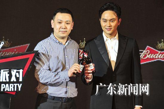 """4月30日,百威华南事业部总裁周臻向张智霖授予""""坚持人物""""的称号并颁发礼物。"""