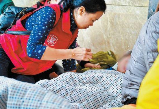 义工照顾在灾害现场外等待失联家人的儿童。 新华社 发