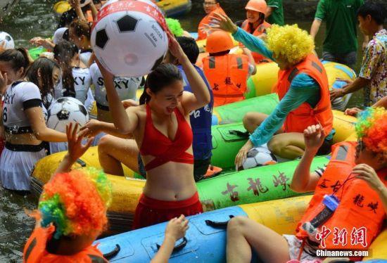 7月10日,来自广州的10名网红主播来到广东清远古龙峡,与200多位球迷在水上玩起了足球争霸赛,争抢水上足球,抢多者为胜。一时间,整个河道里,呐喊声、尖叫声四起,水花四溅,足球满天飞。身穿比基尼的网红主播与戴着假发的球迷争相奔向水里,争抢足球。仅仅几分钟,几百个足球就被一抢而空。连青 摄
