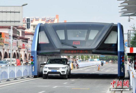 """9月5日,中国自行设计研制的""""空中巴士""""――""""巴铁1号""""在河北秦皇岛综合试验以来,引发国内外广泛关注。据巴铁知识产权所有方、""""巴铁科技""""发言人李楠表示,现场这套测试线路至少还要续留一年以上的时间,还需要进行一些测试、展示和数据采集。计划2017年开放这条道路,让社会车辆从""""巴铁""""线路下方通行,普通市民可以直接参与到""""巴铁""""整个测试过程。图为一辆越野车从测试中的""""巴铁""""下方通过。 中新社记者 翟羽佳 摄"""