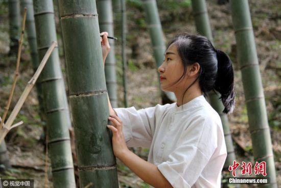 """10月7日,广东清远,不少游客在竹林刻字。国人旅游喜欢刻字作画,""""到此一游""""成为国人的陋习,成为不文明旅游的标签。从现在开始,喜欢刻画的游客就可以到位于广东连山壮族瑶族自治县的金子山特意将一片竹海定位为""""刻字林"""",游客可以在20多亩的竹海里的竹子上刻字、画画,喜欢刻什么就刻什么。刻竹林开放两天,就有100多根竹子刻上了字,内容五花八门,多以示爱为主。曾令华 摄 图片来源:CFP视觉中国"""