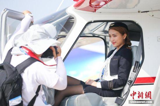 """2016年11月1日,广东省珠海市,第十一届中国国际航空航天博览会(珠海航展)开幕,众多参展商在参展飞机前安排了性感靓丽的""""飞机模特"""",吸引参观者的围观留影。中新社发 许康平 摄 图片来源:CNSPHOTO"""