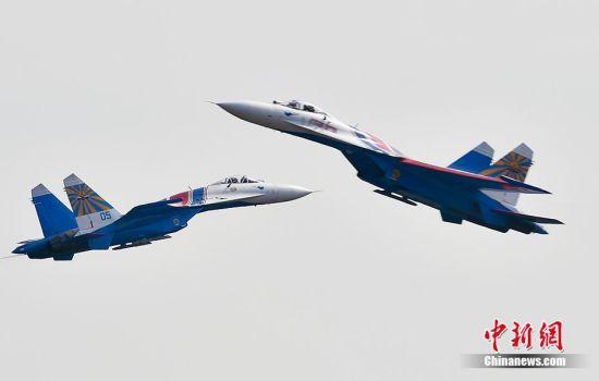 """双机交叉分开对头:两架战机对正观礼台,两机取正高度差5-7米、编成大间隔梯队,距观礼台500米处,以80度交叉分开。之后,两机以30米高度、1300千米/小时相对速度对头掠过。图为2016年11月1日,第十一届中国航展将在广东珠海国际航展中心开幕。俄罗斯""""勇士""""表演队的苏27进行飞行表演。中新网记者 金硕 摄"""