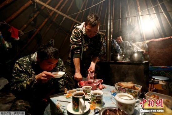 11月27日,牧民们在帐篷里生吃鹿肉。