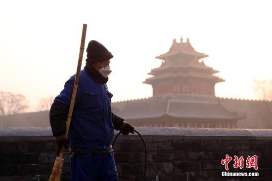 环卫工人在雾霾中清扫街道。 中新社记者 韩海丹 摄