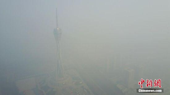 """连日以来河南郑州被雾霾笼罩,12月18日,河南郑州仍是雾霾围城,有着城市地标之称的""""大玉米""""和河南广播电视发射塔纷纷隐身于雾霾之中难觅影踪。图为隐身于雾霾之中的河南广播电视发射塔。 王中举 摄"""