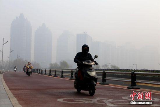 民众在雾霾中出行。 王中举 摄