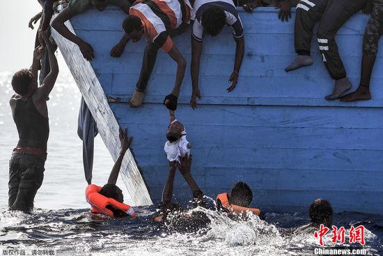 生命托举 2016年10月4日,利比亚海岸,移民在等待救援时将一个孩子托出水面。意大利海岸警卫队宣称,至少1800名移民在救援行动中获救。