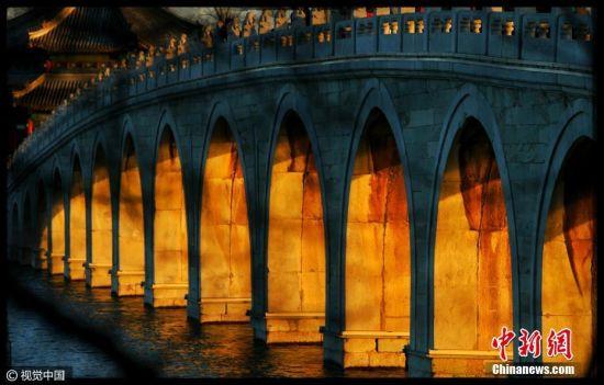 2016年12月28日,北京,建造颐和园的设计师经过精心计算,使十七孔桥与南回归线的日落点呈垂直状态,所以每年冬至前后几天里,落日的余晖将全部照亮十七孔桥的所有17个孔洞,呈现出壮丽景观。李建泉 摄 图片来源:视觉中国