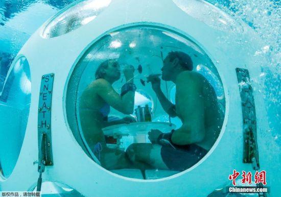 """当地时间2017年1月30日,比利时布鲁塞尔,Nicolas Mouchart 和Florence 穿上了潜水装备和脚蹼,潜入水下餐厅""""珍珠""""用餐。比利时首都布鲁塞尔的 Nemo33 泳池是全球最深的游泳池,深达33米,位于水面五米以下,正是著名的水下餐厅""""The Pearl(珍珠)"""",珍珠餐厅形似一个两米宽的白色球形吊舱,悬浮在水中接近池底。食客们只需脱下配重腰带,便能直接游进""""吊舱"""" 。"""