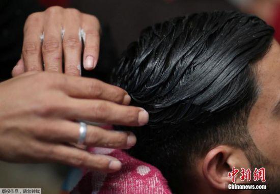 2月2日,在加沙南部拉法难民营一家美发厅,一名巴勒斯坦美发师用火给顾客拉直头发。