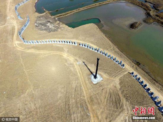 2017年3月13日,山东省滨州市,一处荒地里竖起上百座花岗岩巨石,上面雕刻了金刚经。一根高度超过20米的巨大乌木矗立在场地正中央的位置,直径超过2米。图片来源:视觉中国