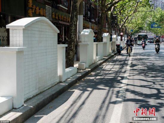 """近日,上海普陀区有居民反映普雄路人行道上一片景观墙造型类似""""墓碑""""。图为4月24日中午,拍摄的这些白色的景观墙。 王冈 摄 图片来源:视觉中国"""