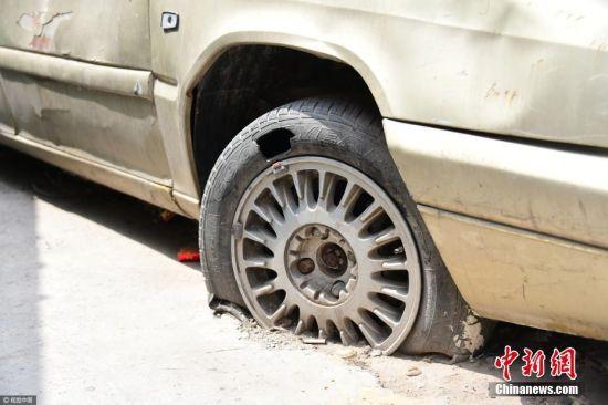 2017年4月26日消息,郑州郑密路淮河西路耿河小区7号楼前,一辆汽车停放十多年未动。小区路面硬化时找不到车主,无人移车,汽车的轮子被砌进水泥路面。此车已经彻底报废,不仅影响居民出行,还存在安全隐患,职能部门不得已贴出通告,希望车主一周内自行处置,否则将会同相关部门按无主车处理。李四信 摄 图片来源:视觉中国