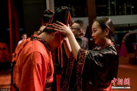 """2017年4月25日,北京某国际学校2017届高三学生成人礼,数百名高三学生在家长的陪伴下走上红地毯跨过""""成人门"""",以中西合璧式的毕业仪式,开启同学们奔赴美国、英国和加拿大等西方国度的本科留学生涯。詹敏 摄 图片来源:视觉中国"""