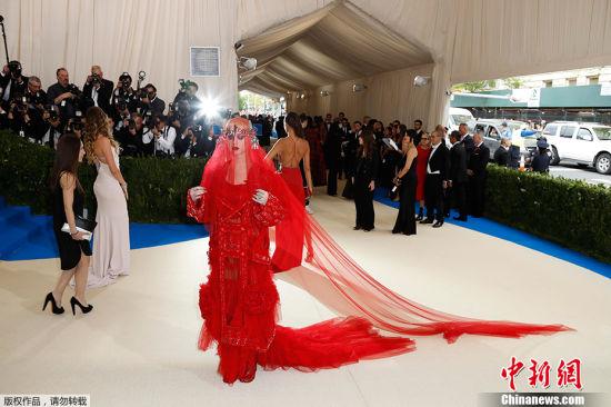 """当地时间2017年5月1日,美国纽约,2017Met Gala纽约大都会艺术博物馆慈善舞会举行,Met Gala是时尚界最隆重的晚会,每年的慈善晚会红毯部分都被誉为""""时尚界奥斯卡"""",入场券高达25000美金。此次的宴会着装主题是川久保玲,可想而知红毯上各路时髦""""女妖精""""们必定包装到每根发梢,活生生的上演一出""""群魔乱舞""""的时装好戏。图为凯蒂・佩里大红纱裙亮相搞怪惹眼。"""