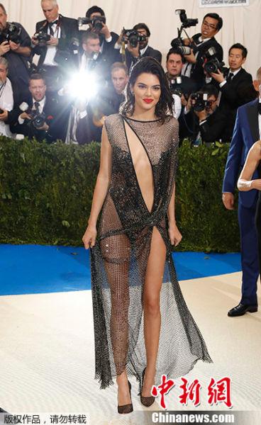 """当地时间2017年5月1日,美国纽约,2017Met Gala纽约大都会艺术博物馆慈善舞会举行,Met Gala是时尚界最隆重的晚会,每年的慈善晚会红毯部分都被誉为""""时尚界奥斯卡"""",入场券高达25000美金。此次的宴会着装主题是川久保玲,可想而知红毯上各路时髦""""女妖精""""们必定包装到每根发梢,活生生的上演一出""""群魔乱舞""""的时装好戏。图为肯达尔・詹娜高开叉透视礼服性感撩人。"""