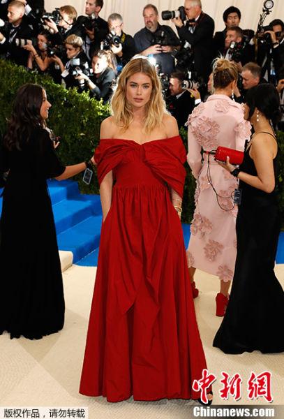 """当地时间2017年5月1日,美国纽约,2017Met Gala纽约大都会艺术博物馆慈善舞会举行,Met Gala是时尚界最隆重的晚会,每年的慈善晚会红毯部分都被誉为""""时尚界奥斯卡"""",入场券高达25000美金。此次的宴会着装主题是川久保玲,可想而知红毯上各路时髦""""女妖精""""们必定包装到每根发梢,活生生的上演一出""""群魔乱舞""""的时装好戏。图为杜晨・科洛斯红色褶皱一字肩长裙亮相。"""