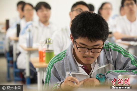 """2017年5月23日,庄逸是杭州某校高三班的学生,曾因三门选考科目都拿满分人送外号""""庄三百""""。6月新高考临近,庄逸复习时用的是自己编写的《高中数学学习参考》,此书高三年级有40人正在使用。图片来源:视觉中国"""