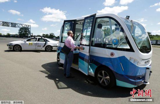 """当地时间7月3日,法国拉德芳斯,一辆由法国初创公司Navya与公共交通提供商Keolis合作生产的电动无人驾驶公交车""""Arma""""在拉德芳斯街道""""亮相"""",在一条专用线路上开展为期6个月发测试。图为2017年6月21日,美国密歇根大学内正在使用的电动无人驾驶公交车""""Arma""""。"""