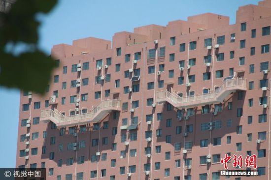 2017年7月10日,在山东济南北园大街上,一幢大楼四个楼梯半悬在50米高的空中,令不少路人看到后直呼心惊胆颤,也不敢走这种楼梯。图片来源:视觉中国