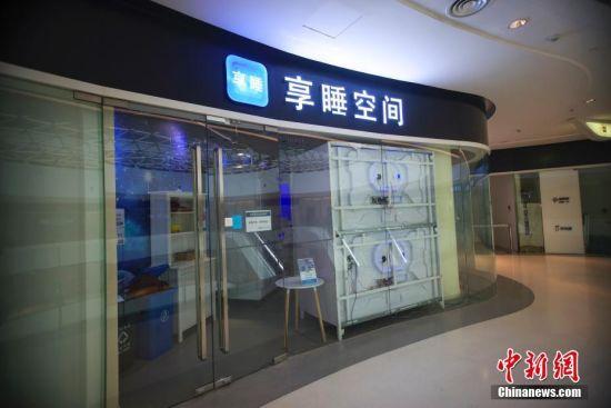 """7月17日,北京一家名为""""享睡空间""""的店铺处于停业状态。在这间10平方米左右的店内,有8个白色的""""太空舱"""",使用者可通过扫描二维码入""""舱""""休息。""""舱""""内提供空调、WIFI、充电插座、阅读灯、一次性床品等设施。中新社记者 贾天勇 摄"""