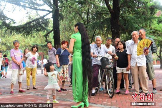 7月30日,河南郑州,郑州建设路与工人路附近,拥有近两米长秀发的樊女士,一出现在大街上和公园里,就引来了众多市民驻足观看,大家惊叹她一头秀发的同时,更敬佩她25年的坚持。今年49岁的樊女士从24岁那年开始留长头发,到如今最长的头发已经超过1.93米,她将继续留下去,看看头发能否超过她的两个身高。图片来源:Sipaphoto 版权作品 禁止转载