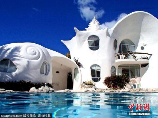 """近日,来自建筑师Eduardo Ocampo的""""贝壳屋"""",不仅整体房屋外形充满贝壳元素,房内装饰也是满满的海洋气息。整栋房子有两座建筑组成,看起来都像贝壳,门窗都是手工雕刻的,使得这里看起来像电影里的场景。而且还有个以鱼类为主题的户外游泳池和烤肉区域。这里的卧室有两个,摆放着特大号的床,洗手间装饰也十分有特色,墙面的装饰灵感则是来自美人鱼。当然这里肯定有WIFI和空调,租客不必担心。 图片来源:Sipaphoto 版权作品 请勿转载"""