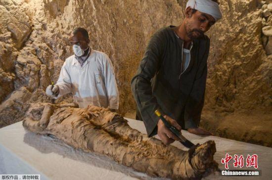 """当地时间2017年12月9日,埃及考古人员在尼罗河西岸的德拉阿布纳加(Draa Abul Naga)墓穴群中新发现""""Kampp 150""""墓穴和""""Kampp 161""""墓穴,木乃伊、古埃及木制葬礼面具和小雕像,以及古埃及女神伊西斯(Isis)的木质雕像等多种文物出土。"""