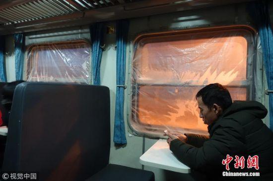 12月25日消息,呼伦贝尔,从海拉尔到根河的旅客列车的车窗全部粘上了一层塑料布。据列车长介绍,因为天气太冷,车体老旧,窗缝透风,加足马力地烧锅炉也不行,为了不让旅客受冻,只能这样做。图片来源:视觉中国