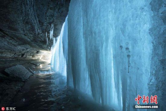 2018年1月8日报道(具体拍摄时间不详),41岁的摄影师Chad Rieder前往美国明尼苏达州,拍摄冰冻住的明尼哈哈瀑布静态之美。Chad Rieder赶在日出时分,拍摄到初阳照射下的冰瀑美景。阳光照在瀑布上,将一道深蓝色的光投射到瀑布后面的岩石上,呈现出绝美意境。图片来源:东方IC 版权作品 请勿转载