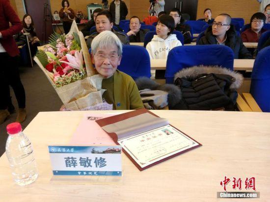"""薛敏修在1957年与1959年先后两次参加高考,却因各种因素未能入学。恢复高考以后,她又受限于""""未婚,年龄低于25岁""""的报考条件。60年过去了,她依然记得当年的梦想,并实现了它。图为薛敏修在毕业典礼上。 中新社记者 张道正 摄"""