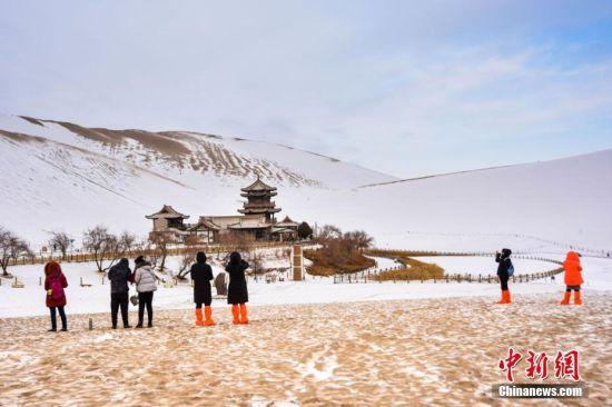 """2月20日凌晨,常年干旱少雨的戈壁城市甘肃敦煌迎来了一场少有的春雪。这场春雪滋润了敦煌大地,也为敦煌著名的鸣沙山月牙泉景区披上了洁白的""""盛装"""",如画的大漠雪景,吸引了众多游客来此欣赏大漠美景,体验别样的丝路风情。据敦煌市旅游局统计,今年春节期间,敦煌日均接待游客达2000人次以上,形成了敦煌春节假日旅游的小高潮。王斌银 摄"""