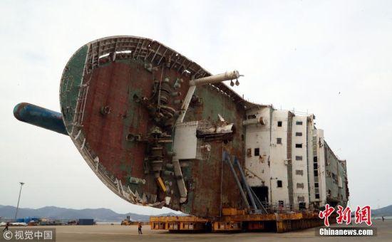 """当地时间2018年2月21日,作业人员在韩国全罗南道木浦新港准备将""""世越""""号移动至模件运输车(MT)上。当天将""""世越""""号打横移动后,工作人员准备于5月31日扶正船体。 图片来源:视觉中国"""