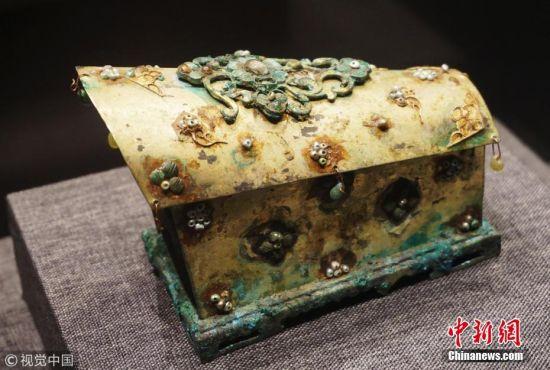 """近日,""""佛影湛然――西安临潼唐代造像七宝""""特展在位于杭州的浙江省博物馆展出,共展出来自西安临潼庆山寺地宫出土的以金棺银椁为代表的盛唐时期精品文物120件,展现了盛唐时期时期的中西文化交流的盛况。 据了解,庆山寺的营建由一场特异的自然灾害催生。在《旧唐书・五行志》记载中,武则天当政时期,位于都城长安境内的新丰县东南露台乡曾有伴随着风雨、冰雹的地震,地震中一座山峰从青原上踊起,高约67米。武则天认为这是吉祥之兆,说山踊现象是上天对她统治成果的肯定。她下令将此山命名为庆山,新丰县也被改名为庆山县。趁此机会,武则天还下令修建一座全新的寺院,取名""""庆山寺"""",地宫亦同时兴建。 庆山寺由建造大明宫的工匠们按照皇家寺院建制,开凿地宫用于供奉舍利。在武则天掌权期间,庆山寺香火鼎盛、高僧云集,成为长安东部最为重要的寺院,有""""东庆山,西法门""""之说。然而,与受李唐宗室世代供养的法门寺不同,武周政权倒台后,庆山寺很快由盛而衰。到了会昌五年(845年),唐武宗颁布""""灭佛""""法令,一大批寺院被毁,恢弘的庆山寺也难逃厄运,最终消散得无影无踪,只剩下深埋地下的地宫,将一部分珍宝保留了下来。地宫则到1985年无意中被人发现,震惊世界。图为2月27日拍摄到的西安临潼庆山寺地宫出的唐代金棺。 龙巍 摄 图片来源:视觉中国"""