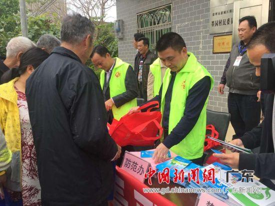 图为惠州市横沥镇党委副书记余广兴与志愿者在墨园村向村民发放禁毒宣传材料。