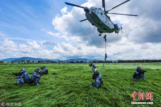 2009年至2017年,摄影师在海南某地记录了蛟龙突击队的影像。蛟龙突击队作为海军陆战队的一支海上特种作战力量,主要担负特种侦察、引导打击等多样化军事任务。与大军团作战方式不同,蛟龙突击队一般都以小组为单位,隐蔽地渗透到敌人后方执行任务,队员必须要练就过硬的综合素质、顽强的意志力、超强的专业技术水平以及团队协作能力。突击队员的训练课目涵盖了陆地、空中、水上、水下四个空间维度的体能技训练。图为班组直升机索降。 孙宏韬 关亚斐 摄 图片来源:视觉中国