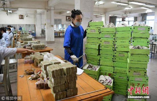 为了公平起见,每天早上,点钞员通过抓阄领取任务。登记好个人私款后进入工作间,手机不能带,工作过程中也要保持安静。点钞时,一大摞碎票倒在桌上,根据不同币种和面值进行分拣清点,以100张同等面值扎为一把,五把为一捆。碰到残币时要用胶布粘起来。有些乘客投币时,把钱叠成五角星等五花八门的形状,点钞员要一点点的拆开。点钞整理后再由复核员进行复核。黎寒池 摄 图片来源:视觉中国