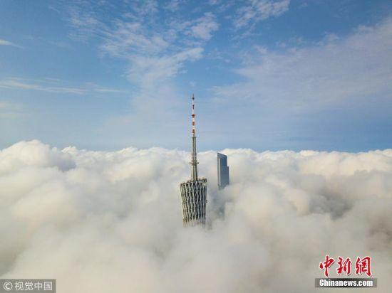 """2018年3月19日,广州城区迎来强对流天气,一场暴雨过后,云雾上出现蓝天,伫立的""""小蛮腰""""电视塔和东塔穿过云层,恍若仙境。 张由琼 摄 图片来源:视觉中国"""
