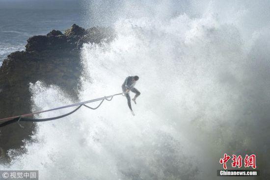 2018年3月22日消息,葡萄牙娜萨瑞,冒险家Andrey Karr挑战架在两处悬崖中间高15米、长达30米的扁带行走。图片来源:视觉中国