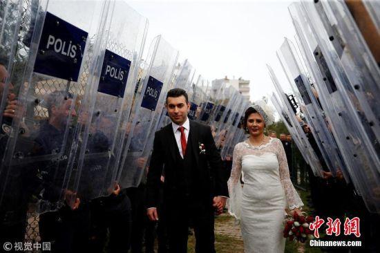 当地时间2018年3月21日,土耳其安塔利亚,警官Ceren Ekici和Taha Yasin Gul举行婚礼。在10个月前的一次行动中,Taha Yasin Gul不慎开枪击中Ceren Ekici的头部,所幸没有造成生命危险。他们的婚礼由警局同事操办,同事们举着防弹盾牌,护送这对新人走向礼台。图片来源:视觉中国