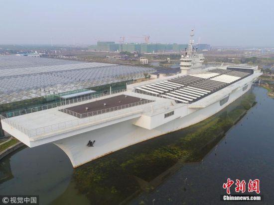 """近日,一艘体型巨大的""""航空母舰""""出现在上海浦东临港地区,该航母紧邻鲜花港的一处绿地中,游人从远处经过,仿佛是一艘真正的航空母舰经停此处。 据悉,该""""航母""""其实是一座钢筋水泥浇灌的""""航空母舰""""外形的建筑。该建筑长度约100米,高度超过10米,外形酷似航空母舰,舰体上舰桥、雷达、火炮一应俱全,十分逼真。目前甲板上都是太阳能板,建筑内部则是一座剧场,入口处上方悬挂着""""航母剧场""""四字标牌。 沈春琛 摄 图片来源:视觉中国"""