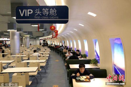 """4月11日,走进南京一高校第五食堂的""""VIP头等舱""""餐厅,随处可见""""登机口""""和VIP头等舱""""的牌子,拱形墙面形似机舱,搭配绿色皮革质地的沙发,每个舷窗上绘有魔幻的星空图,让人体验一下坐在飞机舱里吃饭的感觉,食堂的逆天颜值备受学生青睐。 贾世清 摄 图片来源:视觉中国"""