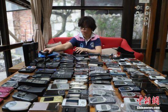 """5月6日,贵州省贵阳市80后女子王祝是一位老数码产品""""发烧友"""",她热衷收集各个年代的手机。从2003年开始收集老式手机以来,15年间,她总共花8万余元收集了300多台。她说希望开一家""""时光博物馆""""。图为王祝正在整理收藏的部分手机。 中新社发 瞿宏伦 摄"""