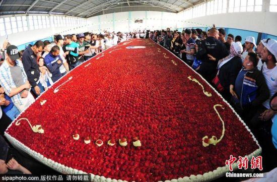 当地时间2018年5月14日,世界上最大的草莓派在阿尔及利亚诞生,在距阿尔及尔300公里的Jijel,蛋糕师们花费了7个小时,造出了这个长达47.79米,宽3米的巨型草莓派。 图片来源:Sipaphoto版权作品 禁止转载