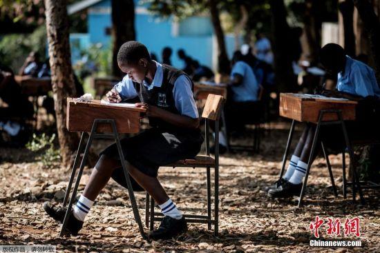 当地时间5月31日,肯尼亚基苏木中学生因为教室过于拥挤而在室外进行英语考试。